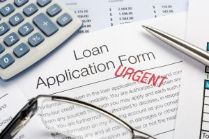 Urgent Loan Application Form with pen, calculator